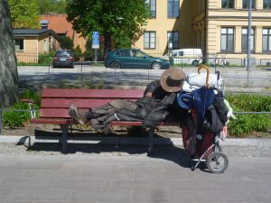 homeless person on a street bench with a shopping trolley holding all their personal possessions next to them.