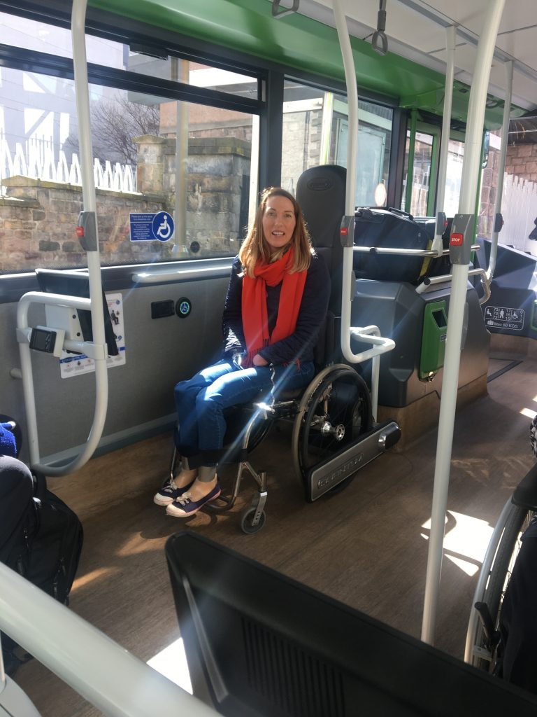 Picture of Helen a wheelchair user trying out the Quantum Lock system for her wheelchair on public transport