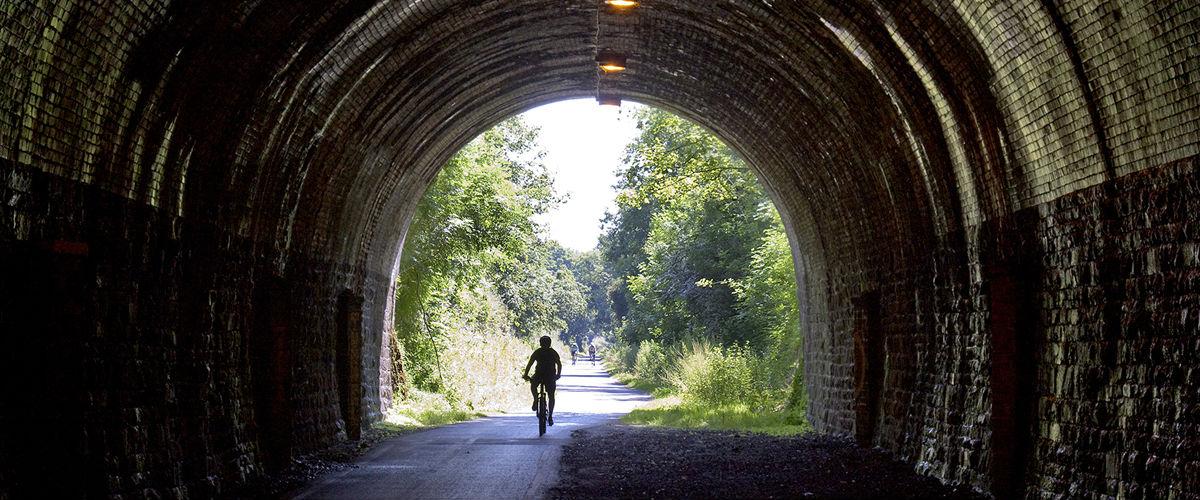 Cyclist riding through Bristol and Bath Railway Path Tunnel