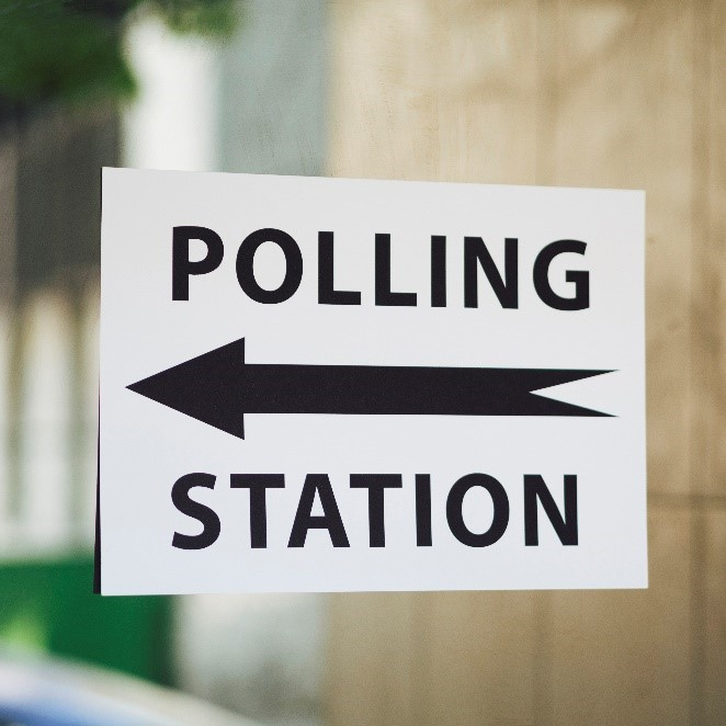 Image of a sign saying Polling Station with an big lack arrow pinting in a westward direction between the words polling and station.