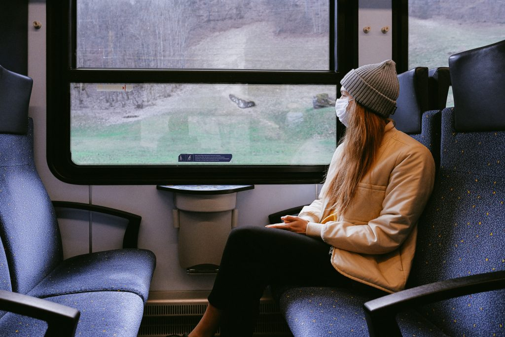 Image of a woman sitting in a train carrage on her own wearing a face mask.