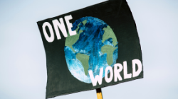 Image of a placard showing a world with the text 'One World'.