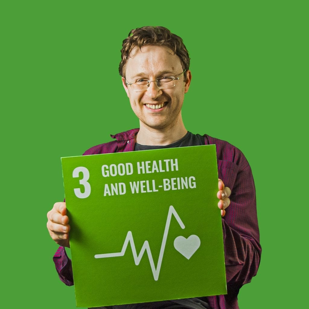 Photo of Dan sitting in front of a bright green background. He's holding up a bright green square shaped placard that reads in white text '3 Good Health and Wellbeing' with a graphic of a heartbeat and heart.